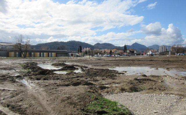Z občine sporočajo, da zemlja, kjer bodo gradili, ni onesnažena. Posebnih zaščitnih ukrepov pri gradnji zato ne načrtujejo in jih že pri urejanju komunalne infrastrukture ni bilo. V neposredni bližini je vrtec Mehurček (nizka pisana stavba v ozadju), kjer bodo avgusta ob strogih protiprašnih ukrepih menjavali zemljino zaradi onesnaženosti. FOTO: Špela Kuralt/Delo