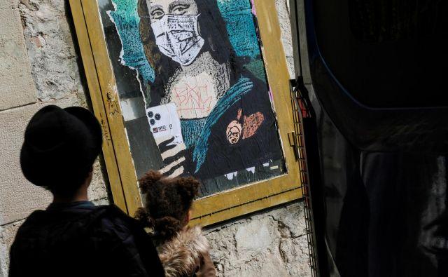 Prizor z ulic Barcelone: otrok in Mona Liza z zaščitno masko. FOTO: Nacho Doce/Reuters