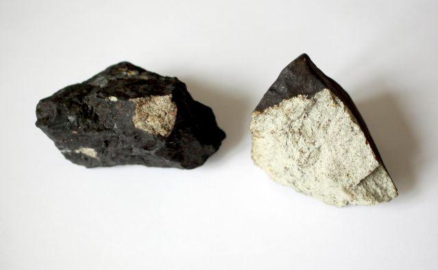 Primerek meteorita z Jesenic. Za meteorite je značilna temna zunanjost in svetla notranjost. FOTO: Roman Šipić/Delo