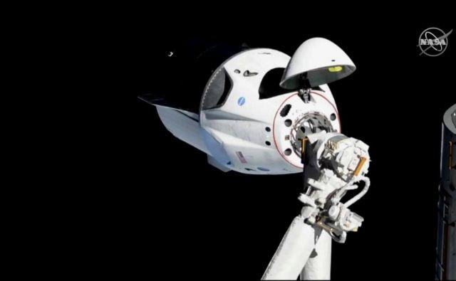 Dragon za človeško posadko ob približevanju postaji lani marca. FOTO: Nasa/Reuters