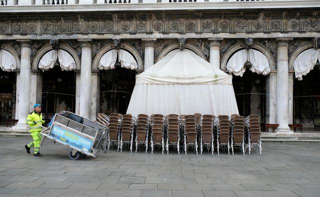 Še pred dnevi so stoli pred restavracijo na osrednjem beneškem trgu čakali na goste, včeraj jih niti razpostavili niso več. FOTO: Reuters