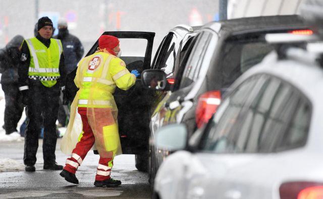 Medicinsko osebje na prelazu Brenner med merjenjem temperature voznikom, ki prihajajo iz Italije. FOTO: Andreas Gebert/Reuters