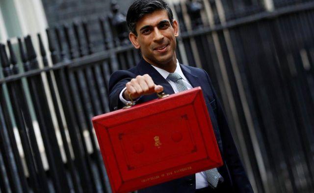 Rishi Sunak 11. decembra pred svojo pisarno na Downing Streetu s proračunskimi dokumenti v tradicionalni rdeči »proračunski škatli«. Foto Reuters