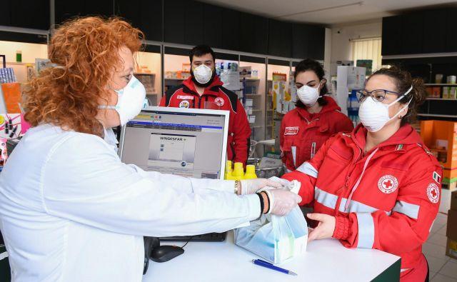 Prostovoljci Rdečega križa kupujejo zdravila za prebivalce kraja Castiglione della Pescaia, ki ne morejo zapustiti svojih domov. Foto Reuters