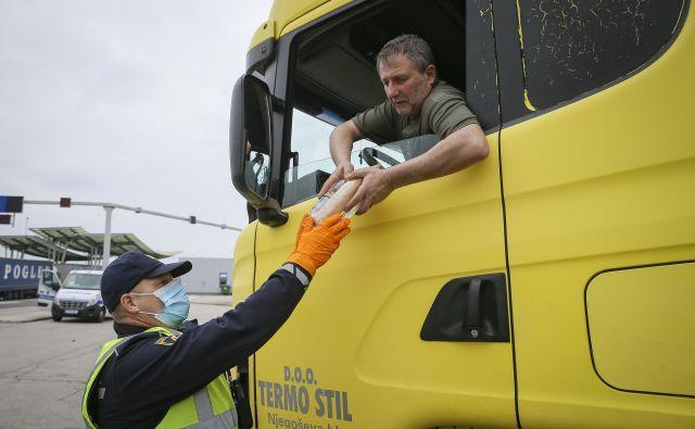 Večina voznikov tovornjakov je po štirih dneh čakanja prvič dobila vodo in sendviče ki jih deli slovenska Policija. Mejni prehod Obrežje 13.3.2020. FOTO: Jože Suhadolnik/Delo