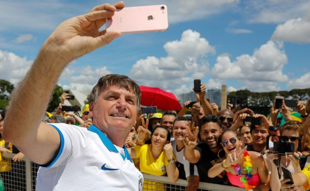 Brazilski predsednik Jair Bolsonaro se je včeraj družil s svojimi podporniki. FOTO: Sergio Lima/AFP