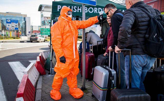 Strožji režim je na notranjih in zunanjih schengenskih mejah. Na fotografiji poljski zdravstveni delavec meri telesno temperaturo potnikom na meji z Nemčijo. FOTO: Odd Andersen/AFP