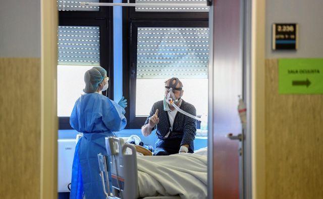 Zdravstvena delavka oskrbuje pacienta z boleznijo covid-19 v bolnišnici Oglio Po v Cremoni. Foto: REUTERS/Flavio Lo Scalzo