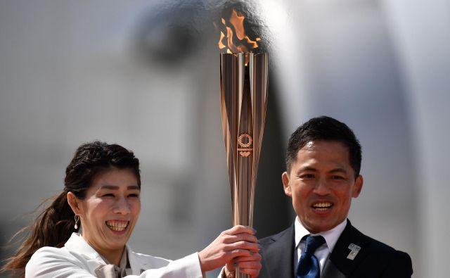 Olimpijski ogenj sta na Japonskem sprejela trikratna olimpijska prvaka, rokoborka Saori Jošida in judoist Tadahiro Nomura. FOTO: AFP
