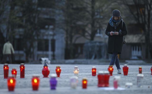 Pozno popoldan so na Trgu republike pred stavbo parlamenta zagorele sveče, ki so jih posamezniki prižigali v znak neodobravanja potez vlade.FOTO: Jože Suhadolnik/Delo