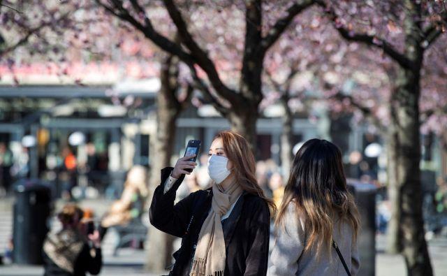 Za Japonce je čustvena vez s češnjevim cvetom preveč pomembna, da bi se odrekli hanamiju. FOTO: Reuters