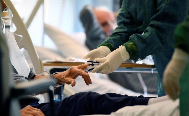 Medicinsko osebje v bolnišnici v Cremoni na severu Italije oskrbuje bolnika obolelega z novim koronavirusom. Foto: REUTERS/Flavio Lo Scalzo