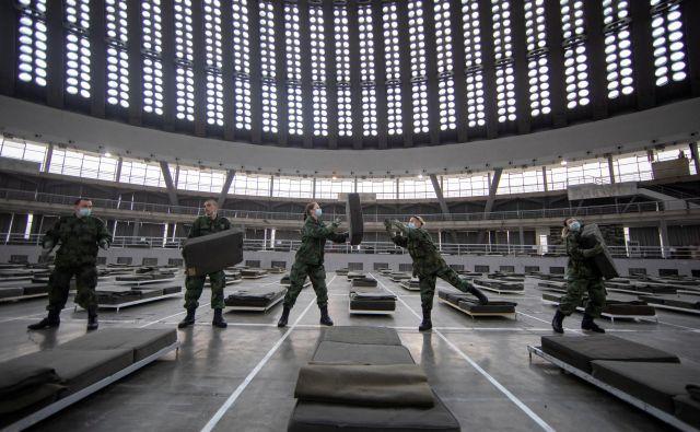 Srbska vojska pripravlja postelje na gospodarskem razstavišču v Beogradu. Foto Reuters