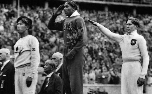 Jesse Owens (v sredini) po olimpijski zmagi v skoku v daljavo, desno srebrni Nemec Luz Long. FOTO: Arhiv MOK