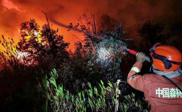 Okrog 1200 kitajskih gasilcev in reševalcev se spopada z gozdnim požarom v pokrajini Sečuan, v katerem je umrlo 19 ljudi. FOTO: Str/Afp