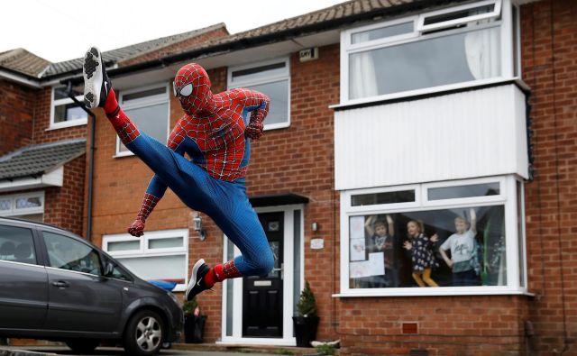 V Stockportu Anglež Jason Baird oblečen v Spidermana med vsakodnevno vadbo razveseljuje lokalne otroke. FOTO: Phil Noble/Reuters<br />