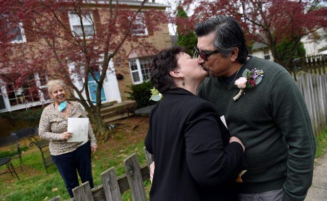 V Arlingtonu v ameriški zvezni državi Virginija se je par poročil kar na pločniku, medtem ko je uradnica, ki je imela masko okoli vratu, slovesnost opravila z varne razdalje na svojem dvorišču. FOTO: Olivier Douliery/Afp