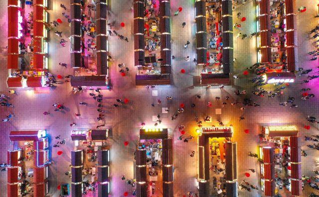 Ljudje med nočnim obiskom tržnice v kitajskem mestu Shenyang. FOTO: Stringer/AFP