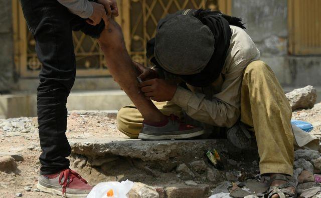 Na ulici v pakistanskem mestuRawalpindi heroinska odvisnika en drugem vbrizgavata heroin. FOTO: Aamir Qureshi/Afp