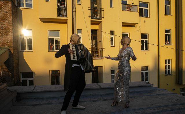 Ulični glasbeniki na strešni terasi ene od stanovansjkih stavb v Pragi igrajo za sosede med samoizolacijo. FOTO: Michal Cizek/Afp