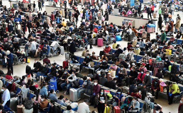 Kitajski potniki čakajo na prevoz na železniški postaji Hankou v Wuhanu po odpravi dvomesečne prepovedi potovanj. FOTO: Stringer/Reuters<br />