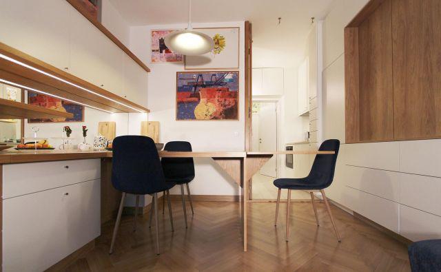 Osrednji prostor je od kuhinje in sanitarij lahko ločen s sklopnimi vrati. Fotografije Jurij Kobe
