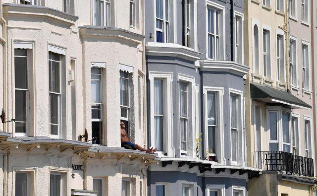 Moški se sonči na okenski polici svoje sobe v Hastingsu, na južni obali Anglije. Bolezen je prišla v osrčje britanske vlade, okužila je več kot 60.000 ljudi po vsej državi, umrlo pa jih je več kot 7.000. 8. aprila so poročali o največjem dnevnem številu 938 smrtnih žrtev. FOTO: Ben Stansall/Afp<br />