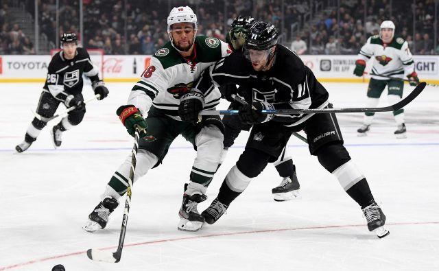 Slovenski hokejski zvezdnik Anže Kopitar (desno; v dvoboju z Jordanom Greenwayem, hokejistom Minnesote) lahko v teh dneh le ugiba, kdaj se bo vrnil na led. FOTO: AFP