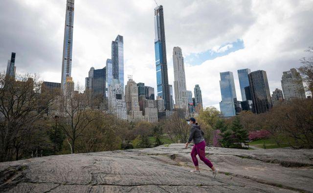 Ženska z zaščitno masko teče po praznem Centralnem parku. Foto AFP