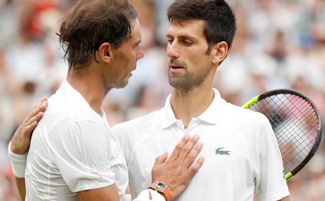 Tako sta se po finalni predstavi Wimbledona pred dvema letoma pozdravila Rafael Nadal in Novak Đoković, zdaj bosta z Rogerjem Federarjem zbirala denar za tiste iz spodnjega dela lestvice ATP. FOTO: Reuters