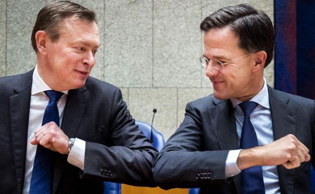 Nizozemski premier Mark Rutte (desno), nizozemski minister za zdravstveno oskrbo Bruno Bruins in njun pozdrav s komolci med sejo spodnjega doma nizozemskega parlamenta. Foto: Remko De Waal/Afp