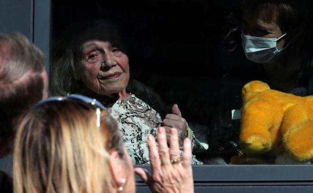 Fotografija iz Bruslja, ki je včeraj ganila Evropo; 92-letna Martha Licoppe iz doma upokojencev pozdravlja svoja otroka Chantal in Christiana. Covid-19 je v domovih za ostarele zahteval kar 3835 žrtev. FOTO: Reuters