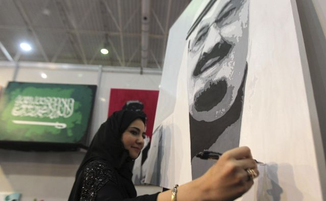 Ženska ustvarja portret kralja Abdulaha. FOTO: Faisal Al Nasser/Reuters