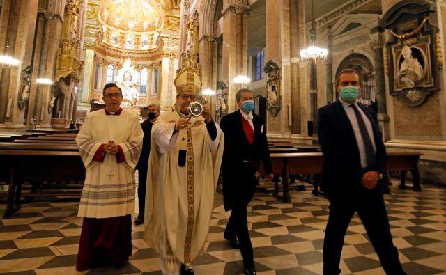 Kardinal Crescenzio Sepe z relikvijo sv. Januarija. Domnevna kri svetnika, mučenca iz časa zgodnjega krščanstva, vernikov tudi med pandemijo koronavirusa ni razočarala. Utekočinila se je že v sefu, v katerem jo hranijo. FOTO: Ciro De Luca/Reuters