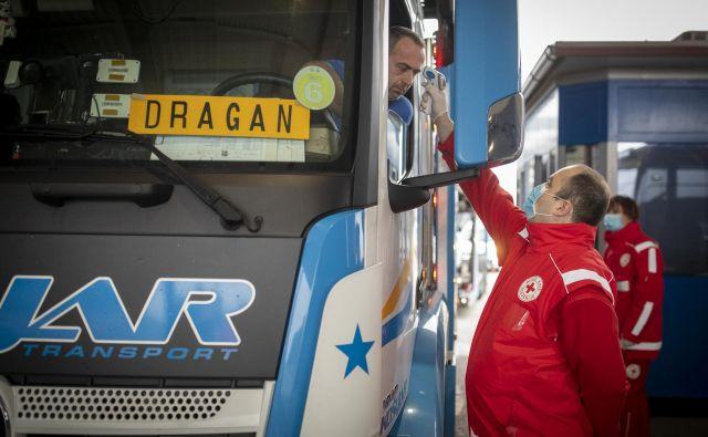 Delavci Rdečega križa in policija na mejnih prehodih izvaja merjenje temperature. FOTO: Voranc Vogel/Delo