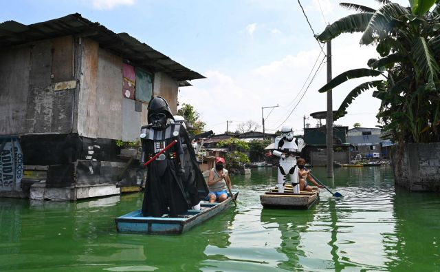 Vaški oficir, oblečen v lik Dartha Vaderja, iz filmske franšize Vojna zvezd, pluje na majhnem čolnu s katerim dostavlja hrano in obleke prebivalcem v poplavljeni vasi Artex v Malabonu na Filipinih. FOTO: Ted Aljibe/Afp