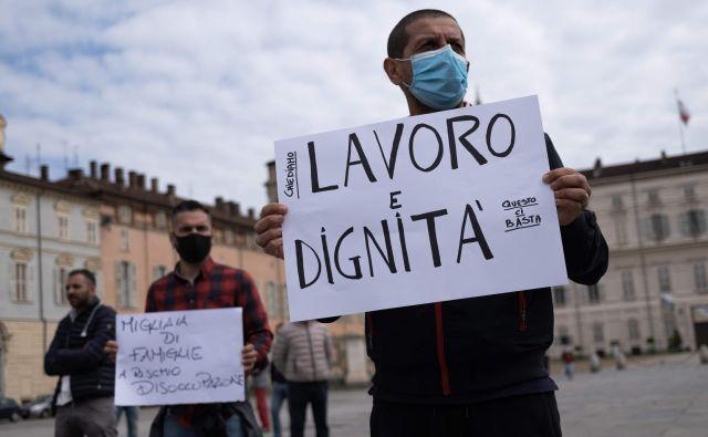 Delo in dostojanstvo, so zahtevali protestniki v Torinu. Pandemija koronavirusa bo imela močne gospodarske in socialne posledice. FOTO: Marco Bertorello/AFP