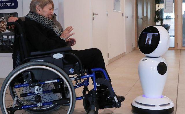 76-letna Belgijka Andree Desmaelle komunicira z domačimi zahvaljujoč robotu, ki ga je belgijsko podjetje ZoraBots brezplačno dalo na razpolago domovom za starejše, ki so na ta način lahko ostali v stiku s svojimi sorodniki zaradi prepovedi obiskov. FOTO: Yves Herman/Reuters