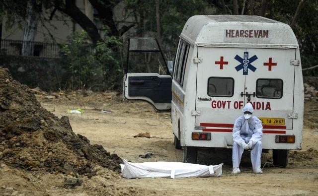 Žrtve je virus zahteval širom sveta, na fotografiji pokop v Indiji. FOTO: Sajjad Hussain/Afp