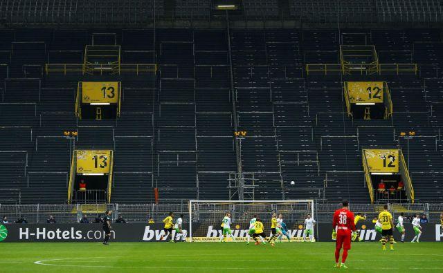 Takole sta pred tremi leti igrala Borussia in Wolfsburg zavoljo ene tekme prepovedi igranja pred navijači, ki je doletela Dortmundčane. Podoben prizor se obeta danes na porurskem derbiju. FOTO: Reuters