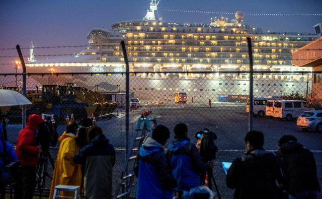 Izbruh novega koronavirusa je križarko Diamond Princess čez noč spremenil v svojevrsten zapor na morju, pričakovanja potnikov in posadke so se sprevrgla v čakanje v kabinah na »križarjenju«, ki ni več vodilo nikamor.FOTO: Athit Perawongmetha/Reuters