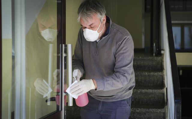 Z vodo in detergentom je še vedno potrebno čistiti kljuke, stikala in ograje, ob vhod namestiti razkužilo za roke, skupni prostori pa se morajo večkrat na dan zračiti. FOTO: Jože Suhadolnik/Delo