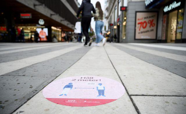 Nalepke na javnih površinah opozarjajo prebivalce Stockholma, naj ohranjajo socialno distanco. Foto:AFP