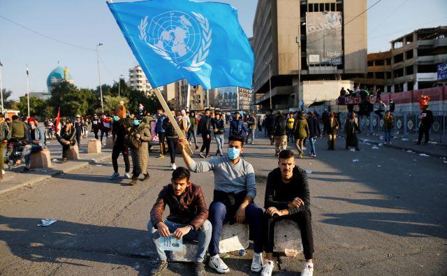 Udeleženec protestov v Iraku z zastavo Združenih narodov. FOTO: Thaier Al-sudani/Reuters