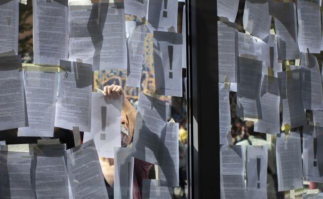 Umetniki so okna ministrske zgradbe prelepili z listi papirja z neodgovorjenimi vprašanji, dopisi, pozivi in pobudami. FOTO: Voranc Vogel/Delo