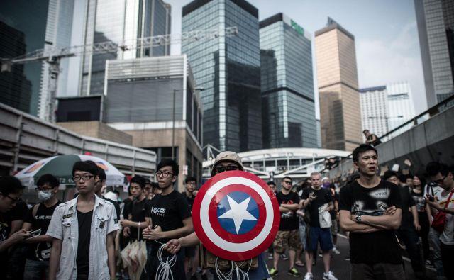 Osredotočenje kitajske na Ameriko pomeni pripravljanje na spopad okoli Tajvana. Na fotografiji protestniki proti Kitajski v Hongkongu z emblemom junaka iz stripov Stotnika Amerike. FOTO:Philippe Lopez/Afp