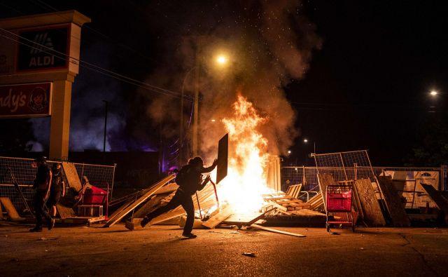 Protestnik pred zažgano trgovino v Minneapolisu Foto AFP