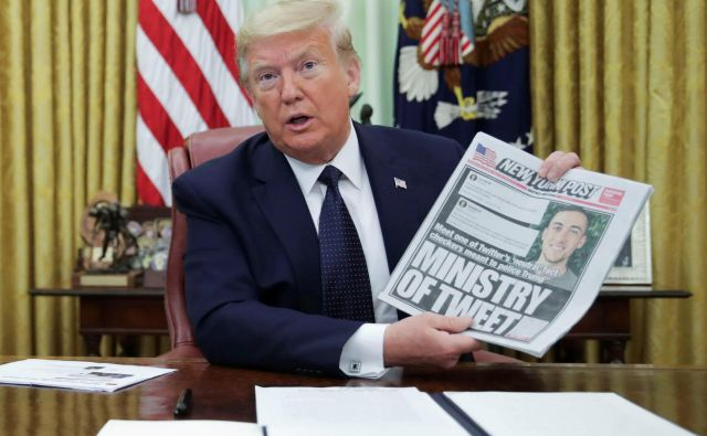 Ameriški predsednik Donald Trump je pred podpisom izvršilnega ukaza razkazoval naslovnico časopisa New York Post.FOTO: Jonathan Ernst/Reuters