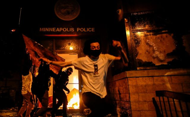 Protestniki so zažgali vhod v policijsko postajo v bližini kraja smrti Georgea Floyda. FOTO:Carlos Barria/Reuters