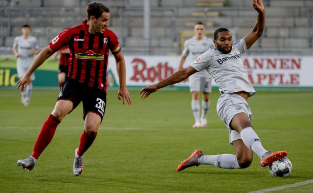 Nogometaši Leverkusna (desno branilec Jonathan Tah) so zabeležili pomembno zmago v Freiburgu. FOTO: AFP